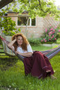 Adult woman resting hammock in garden of country house beautiful smiling Royalty Free Stock Photo