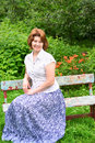 Adult woman sitting on a bench in the garden Royalty Free Stock Photo