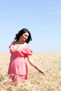 Adult woman in a wheat field beautiful pink sundress Royalty Free Stock Photography