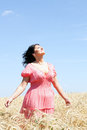 Adult woman in a wheat field beautiful pink sundress Royalty Free Stock Images