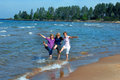 Adults being kids three sisters revisit their childhood and kick and splash in the waters of lake superior in upper peninsula Stock Photography