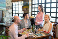 Adults eating out in restaurant happy a fashionable while young and beautiful waitress is serving them Royalty Free Stock Photo