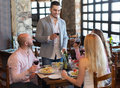 Adults having dinner in restaurant portrait of positive family focus on adult man Royalty Free Stock Photography
