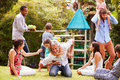 Adults and kids having fun playing in a garden Royalty Free Stock Images