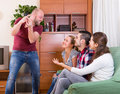 Adults playing charades happy in house and laughing Royalty Free Stock Image