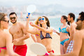 Adults playing paddle games on beach happy summer vacation are with rackets a near blue sea Royalty Free Stock Images