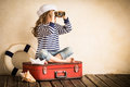 Adventure happy kid playing with toy sailing boat indoors travel and concept Stock Photography