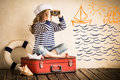 Adventure happy kid playing with toy sailing boat indoors travel and concept Royalty Free Stock Photo