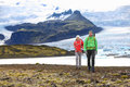Adventure hiking travel couple trekking on iceland people by glacier and glacial lagoon lake of fjallsarlon vatna glacier Royalty Free Stock Images