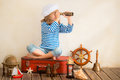 Adventure and travel concept happy child playing with vintage nautical things kid having fun at home summer sea dream imagination Stock Photography