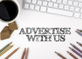 Advertise With Us. White office desk Royalty Free Stock Photo