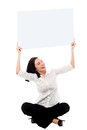 Advertise your business here pretty female sitting on the floor and holding whiteboard above her head Royalty Free Stock Photo