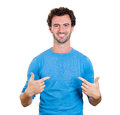 Advertising closeup portrait smiling handsome young happy man student pointing at chest in blank blue shirt isolated white Royalty Free Stock Image