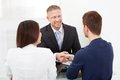 Advisor shaking hand with couple smiling financial young at office desk Stock Photo