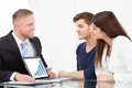 Advisor showing investment plans to couple on laptop male financial at office desk Stock Images