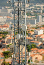 Aerial Antenna telecommunication tower with city behind Royalty Free Stock Photo