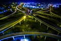 Aerial Highway Interchange Loops and Turn arounds as the City lights grow at Night Speed of Light energizes on a new Road of Techn Royalty Free Stock Photo