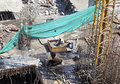 Aerial labourers clearing trash into skip