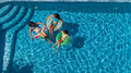 Aerial top view of family in swimming pool from above, mother and kids swim and have fun in water on family vacation Royalty Free Stock Photo