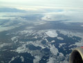 The aerial view of Arctic: blocks of ice in the sea, far snow-covered mountains and clouds. Royalty Free Stock Photo
