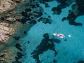 Aerial view of a boat in front of the Mortorio island in Sardinia. Amazing beach with a turquoise and transparent sea. Emerald Coa Royalty Free Stock Photo