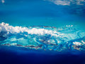 Aerial view of caribbean bahamas islands rising in a turquoise sea covered by line clouds spreading below Royalty Free Stock Images