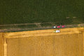 Aerial view of combine harvester unloading harvested wheat Royalty Free Stock Photo