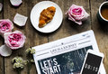 Aerial view of croissant and newspaper with roses decoration on Royalty Free Stock Photo