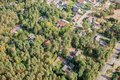 Aerial view of the edge of a village with small family houses, whose properties penetrate into the dense forest. Royalty Free Stock Photo