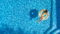 Aerial view of girl in swimming pool from above, kid swim on inflatable ring donut in water on family vacation Royalty Free Stock Photo