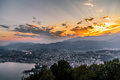 Aerial view of the lake Lugano surrounded by mountains and evening city Lugano on during dramatic sunset, Switzerland, Royalty Free Stock Photo