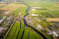 Aerial view over the amsterdam suburbs with canals houses fields and industrial buildings holland Stock Photo