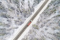 Aerial view of road with red truck in winter forest