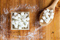 Aerial View of Sugar Cubes in Square Shaped Bowl and Spoon with Unrefined Sugar spill over in Wooden Background. Royalty Free Stock Photo