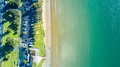 Aerial view on sunny beach with car parking. Auckland, New Zealand. Royalty Free Stock Photo