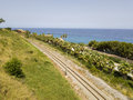Aerial view of train tracks crossing the coast with sea Royalty Free Stock Photo