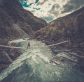 Aerial view of woman standing on the suspension bridge over a wild mountain river. Royalty Free Stock Photo