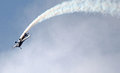 Aerobatic plane. Smoke trail as it does stunts. Royalty Free Stock Photo