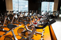 Aerobics spinning exercise bikes gym room in a row with many Royalty Free Stock Photos