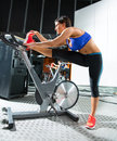 Aerobics spinning monitor trainer woman stretching exercises after workout at gym Stock Photography