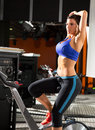 Aerobics spinning monitor trainer woman stretching exercises after workout at gym Royalty Free Stock Photography