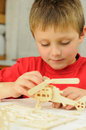 Aeromodeling smart young boy building a wooden helicopter model from kit Stock Photography