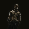 Aesthetic bodybuilding handsome athletic young man isolated on black Stock Photo