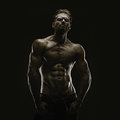 Aesthetic bodybuilding handsome athletic young man isolated on black Stock Photos