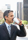 Affärsman drinking takeaway coffee utanför kontor Arkivbilder