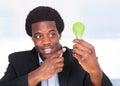 Affärsman holding light bulb med grönt gräs Fotografering för Bildbyråer