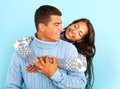 Affection portrait of amorous female embracing her boyfriend over blue background Royalty Free Stock Photos