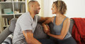 Affectionate black couple talking on couch together Royalty Free Stock Photography