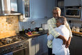 Affectionate couple with eyes closed embracing while standing in kitchen Royalty Free Stock Photo