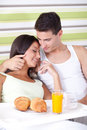 Affectionate couple having breakfast in bed morning Stock Image